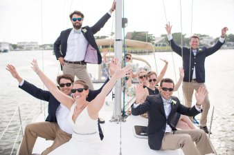 the bridal party arriving to their reception on a sail boat